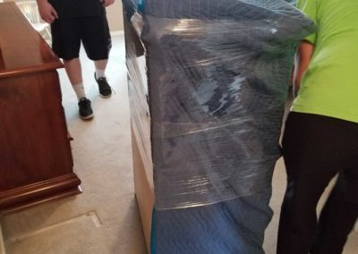 Casey and Ian wrapping an armoire for transport